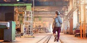 Fabrikarbeiter läuft in Schutzkleidung durch die Fabrikhalle
