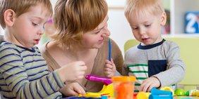 Mutter spielt mit ihren zwei kleinen Kindern