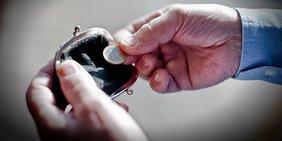 Hände holen einen Euro aus Geldbeutel