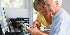 Älterer Mann und ältere Frau im Gespräch während Arbeit vor Bildschirm