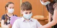 Kinder mit Mund-Nasenschutz in der Schule mit Lehrerin