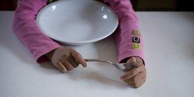 Ein Mädchen sitzt mit Messer und Gabel in den Händen vor einem leeren Teller