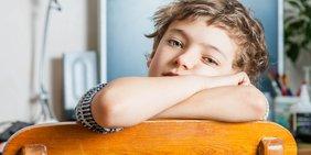 Nahaufnahme eines Jungen, der traurig über eine Stuhllehne blickt; im Hintergrund ein Schreibtisch