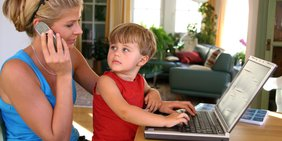 Mutter mit Kind auf dem Schoß und Laptop