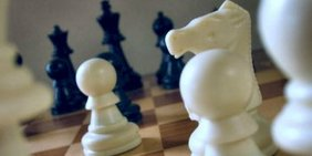 Schwarze und weiße Schachfiguren auf Schachbrett