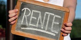 """Frau hält Tafel mit Schriftzug """"Rente"""""""