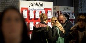Menschen vor Stellenangeboten auf Jobmesse