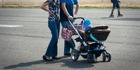 Familie Frau und Mann und Kleinkind im Kinderwagen