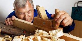 Mann mit Hobel bearbeitet ein Stück Holz