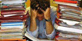 Ein Mann sitzt verzweifelt am voll gepackten Schreibtisch