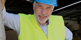älterer Herr, blauer Bauhelm, neongelbe Warnweste, auf Baustelle (lächelnd)