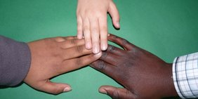 2 farbige nud eine weiße Hand in Kontakt